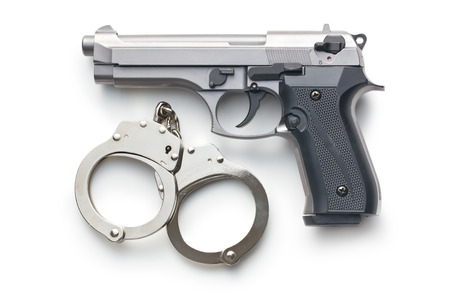 gun and handcuffs on white background Stock Photo