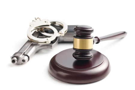 automatic pistol: judges gavel and handgun with handcuffs on white background Stock Photo