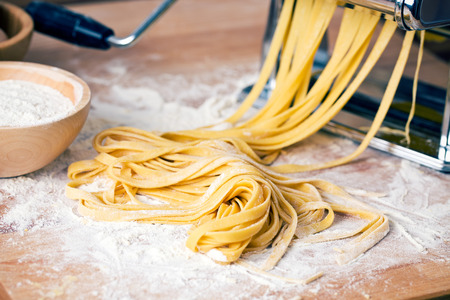 in a raw: fresh pasta and pasta machine on kitchen table