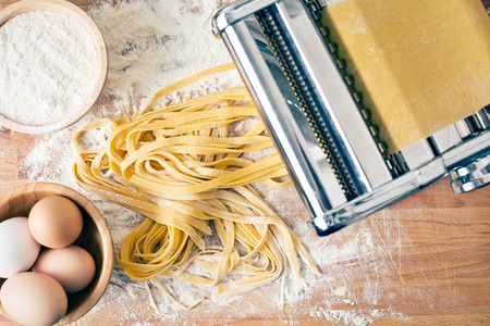 machine: fresh pasta and pasta machine on kitchen table