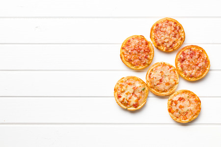 mini pizza: top view of mini pizza on wooden table