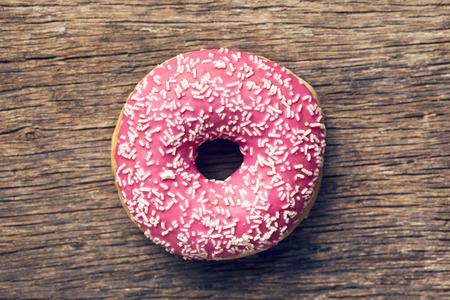 古い木製の背景にピンクのドーナツ