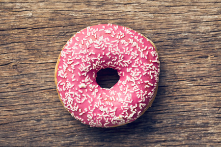 donut: pink donut on old wooden background