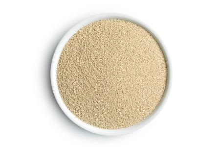 levadura: levadura seca en un recipiente en el fondo blanco Foto de archivo
