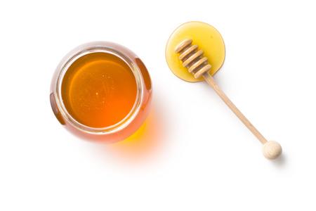 miel de abeja: cuchar�n de miel y miel en tarro en el fondo blanco Foto de archivo