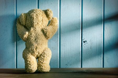 de teddybeer staat voor een blauwe muur
