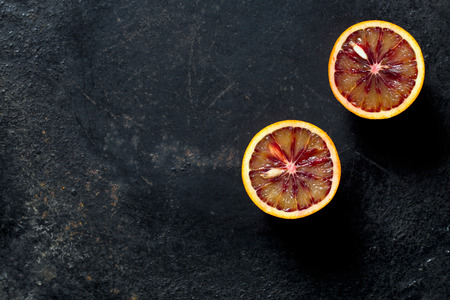 citrous: halved blood orange on black background