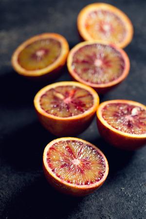halved blood orange on black background