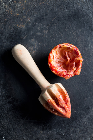 citrous: halved blood orange and juicer on black background