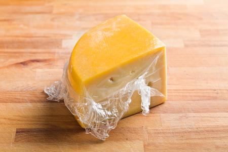 edam: wrapped edam cheese on kitchen table