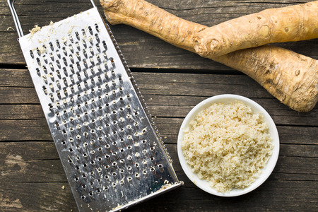 grated horseradish root on kitchen table Zdjęcie Seryjne