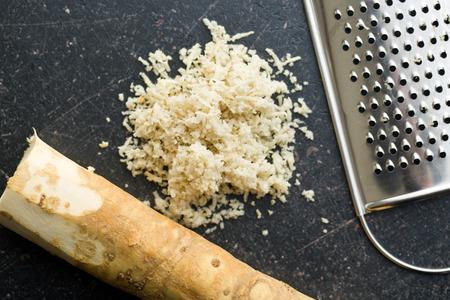 horseradish: grated horseradish root on kitchen table Stock Photo