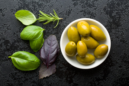 green herbs: green olives and herbs on black table