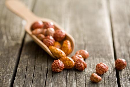 Verschiedene gezuckerte Nüsse in Schaufel auf alten Holztisch