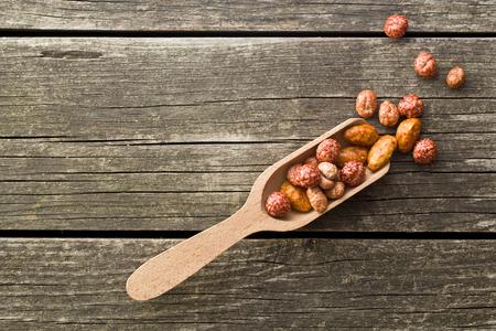 vaus gezuckerte Nüsse in Schaufel auf alten Holztisch