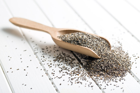 chia seeds in wooden scoop on white table