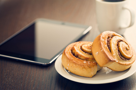 breakfast cup: Cinnamon rolls, cup of coffee and computer tablet. Business breakfast.