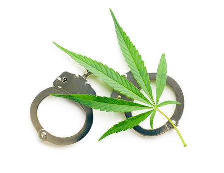 metal handcuffs: the cannabis leaf and handcuffs Stock Photo