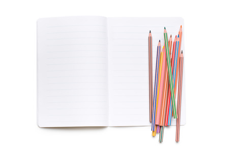 workbook: colored pencils and open workbook on white background Stock Photo