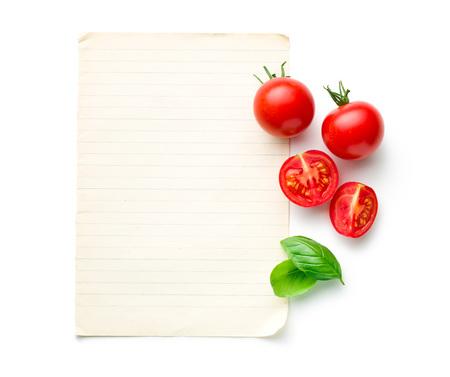 jitomates: el tomate y la albahaca picada hoja con papel en blanco