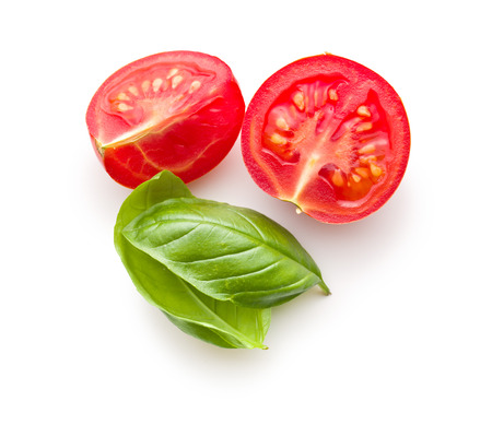 green top: chopped tomatoes and basil leaf on white background
