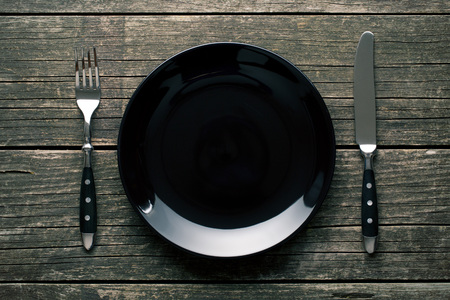 rustic kitchen: empty plate with fork and knife on the vintage wooden table