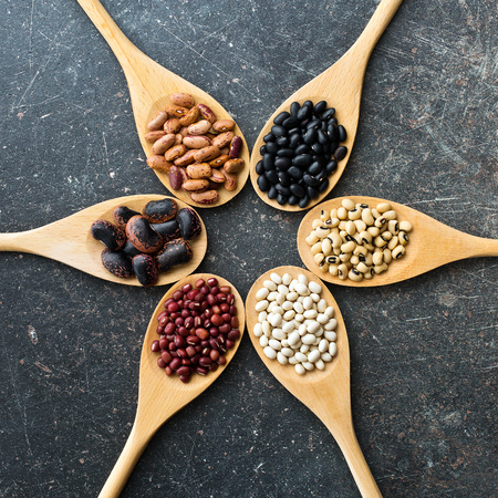 bean: various uncooked legumes in wooden spoons