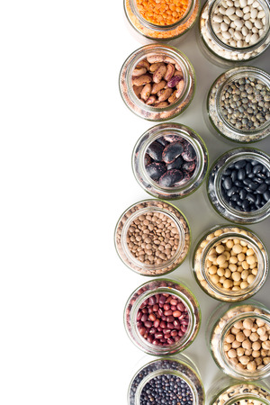 various dried legumes in jars on white background