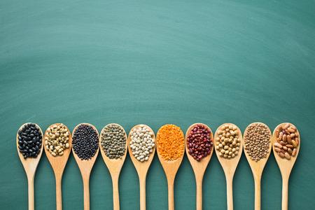 緑の黒板に木製のスプーンで様々 な乾燥豆類 写真素材