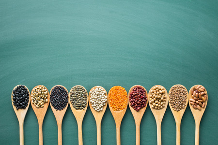 various dried legumes in wooden spoons on green chalkboard