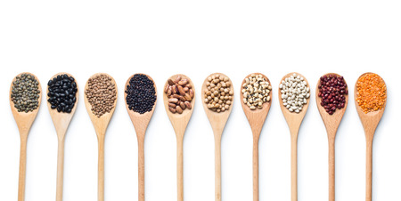 various dried legumes in wooden spoons on white background Foto de archivo