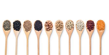 frijoles rojos: diversas legumbres secas en cucharas de madera sobre fondo blanco