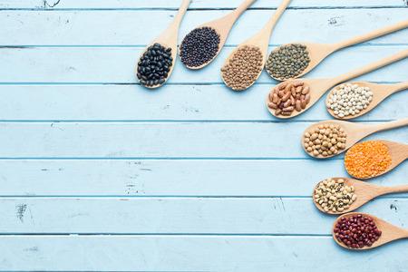 lentejas: diversas legumbres secas en cucharas de madera en mesa de la cocina