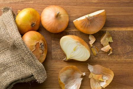 sacco juta: cipolle fresche nel sacco di iuta sul tavolo in legno Archivio Fotografico