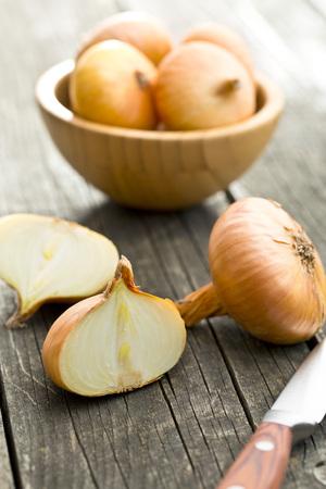 cebolla: cebolla fresca partida en dos en la mesa de madera vieja Foto de archivo