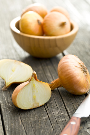 onion: halved fresh onion on wooden old table Stock Photo