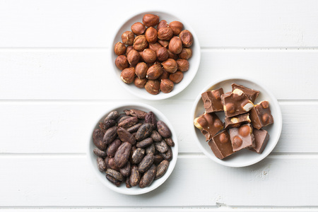 chocolate, hazelnuts and cocoa beans on kitchen table