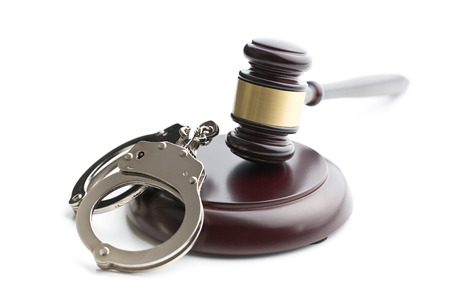 restraints: handcuffs and judge gavel on white background