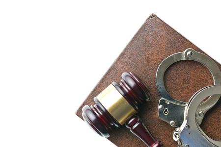 prison system: handcuffs and judge gavel on white background