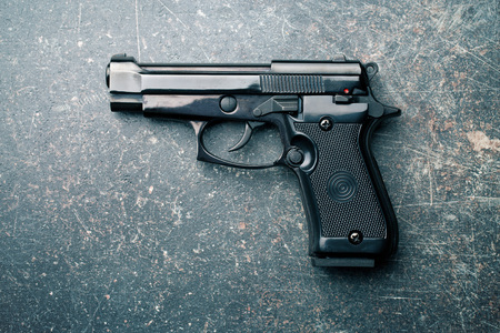 automatic pistol: black handgun on old crackle background