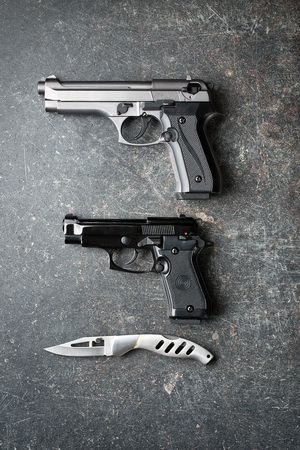 handguns: handguns and offensive knife on old background