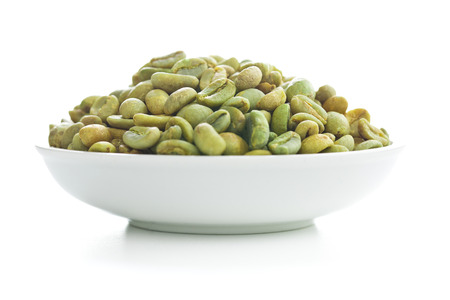 unroasted: unroasted coffee beans in bowl on white background