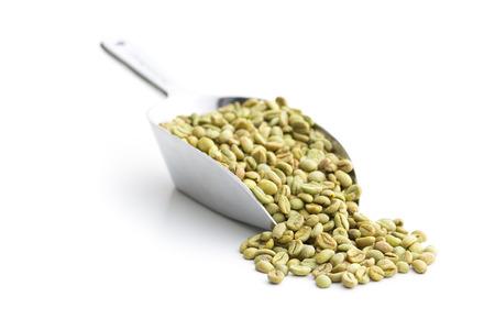 planta de cafe: granos de café verde en cuchara de metal en el fondo blanco Foto de archivo