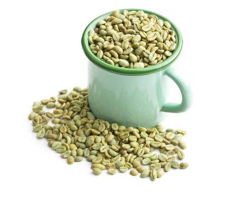 unroasted: unroasted coffee beans in green mug on white background