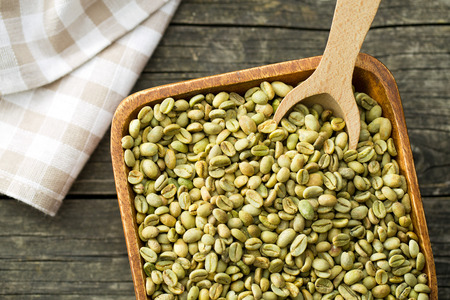 coffee grains: green coffee beans in wooden bowl on old wooden table