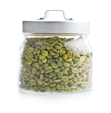 grano de cafe: granos de café verde en el tarro en el fondo blanco Foto de archivo