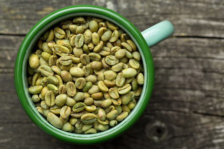 unroasted: top view of unroasted coffee beans in mug