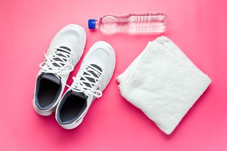 sport concept. fles, schoenen en handdoek op roze achtergrond