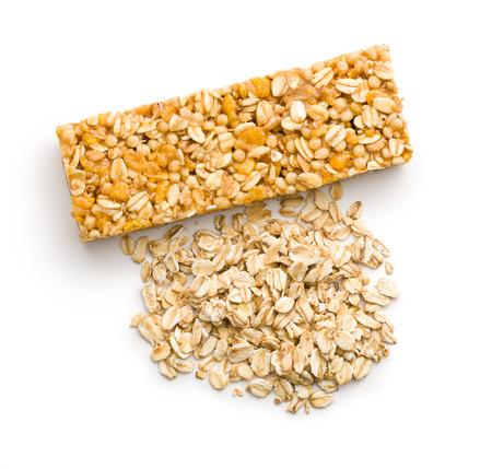 barra de cereal: bar y avena copos de muesli en el fondo blanco
