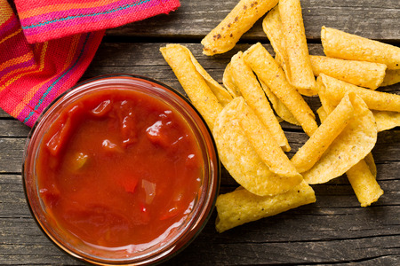 nacho: rolled nacho chips and salsa dip on old wooden table